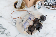 Sunglasses and accessories are arranged on a marble table.