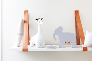 A detail of a white shelf in a nursery with decorative animals.