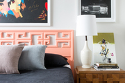A colorful bedroom with a coral headboard.