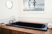 A black-and-white photo hung in a nautical-themed bathroom