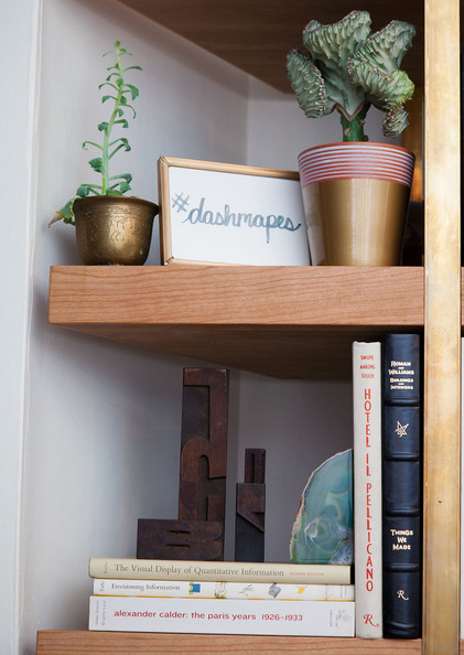Eclectic Bookshelf - Plants, books and decor accents, including a coral catus from Costa Farms and an agate book end by West Elm, are layered on a cherry wood book shelf by Pink Sparrow Scenic