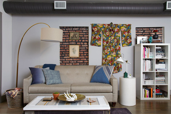 Eclectic Bookshelf - A large gold lamp and hanging kimono frame a beige sofa