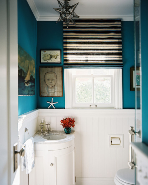 Eclectic - A blue bathroom with a striped roman shade and a corner sink