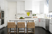 White cabinetry and wicker stools contrasted against a black wood floor.
