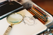 A magnifying glass and art supplies on a desk