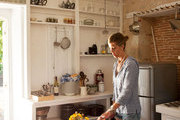 Designer Julia Leach cuts produce in her French kitchen