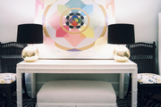 A geometric painting flanked by gold lamps with black shades