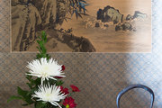 An alcove decorated with antique vessels, fresh flowers, and traditional artwork