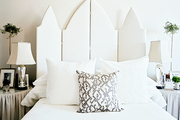 A white upholstered folding screen as a headboard in a neutral bedroom