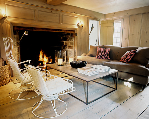 Fireplace - A brown roll-arm couch, a wooden coffee table, and white metal chairs in a paneled living room