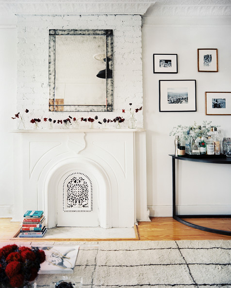 fireplace a mirror over a white mantel beside a tray of bar