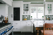 White kitchen cabinetry with a mossy green backsplash and chalkboard door front