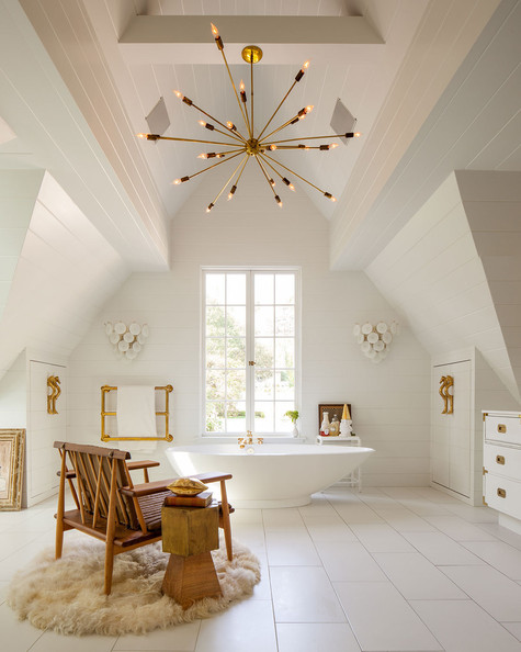 Freestanding Tub - A Sputnik chandelier hanging from an a-frame ceiling with a freestanding tub below