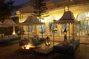 Canopied banquettes and a fire pit in the outdoor seating area of a cocktail lounge in Jaipur