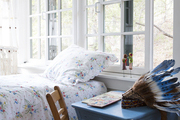 A windowed kids' bedroom with a blue desk