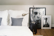 White bedding and a fur throw in a room with black-and-white photography