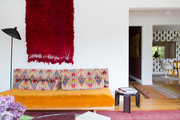 A mustard sofa in an eclectic living area below a red shag wall hanging.