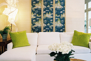 Framed chinoiserie panels above a white sectional couch