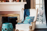 A white wingback chair and a blue garden stool surrounding a white mantel