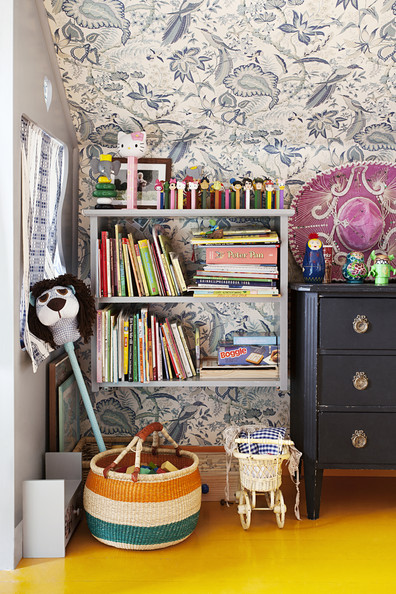 Gray Bookshelf - A shelf of books and toys against floral wallpaper