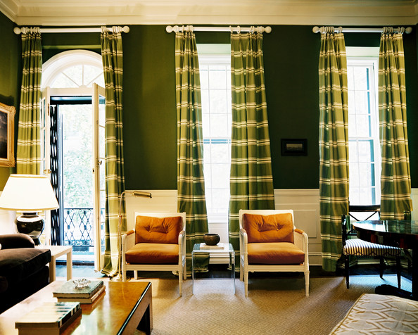 green living room green striped curtains behind a pair of chairs and