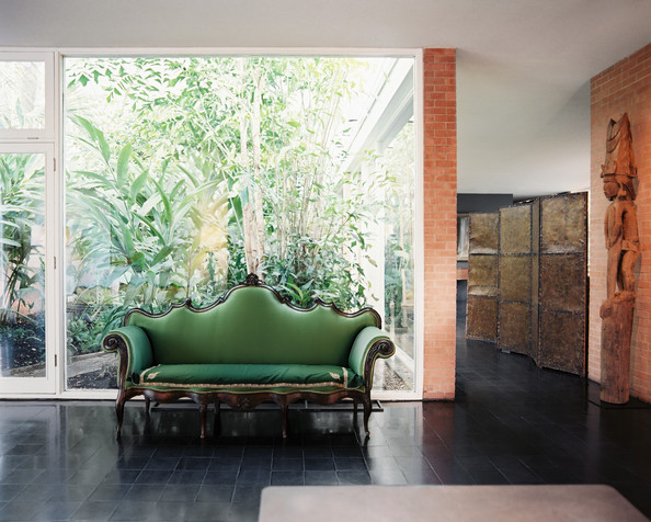 Green Living Room - A green sofa in front of a wall of windows
