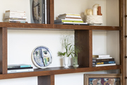 A series of shelves put together into a living area display piece, holding books, photos, and ceramic pieces.