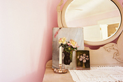 A lace fabric and vintage floral oil paintings sit on an antique dresser with mirror in a pink bedroom.