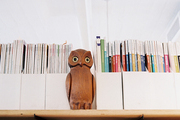 Magazines organized beside a wooden owl