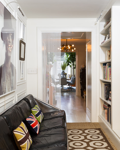 Hallway - A framed artwork and a black leather couch with throw pillows atop area rugs