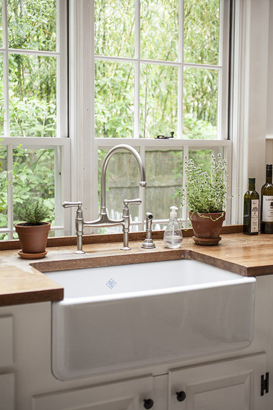 Hardware - An apron-front sink and wooden countertop in a kitchen