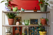 A wooden shelf that holds many colorful pots and plants.