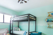 A teal kid's bedroom with a blue rug and chest.