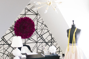 The fashion designer's home office features a mannequin, a juju hat, and a golden pendant light.