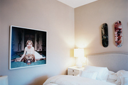 A Slim Aarons photograph and Marilyn Minter skateboard art in a neutral bedroom