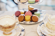 Teacups and macarons stacked on a tiered serving tray