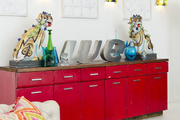 A red console with antique foo dogs and vintage letters under minimalist artwork and midcentury sconces