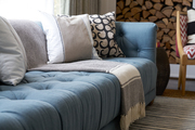 Tuft couch with patterned throw pillows and a striped blanket.