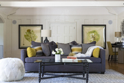 An array of pillows top a dark gray sofa