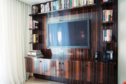 Zebrawood built-in cabinetry containing books and a TV