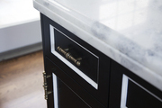 A detail of black-and-white cabinetry with vintage hardware and a marble countertop