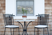 Black and white metal chairs and table on outdoor porch.