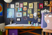 An artist studio showcasing colorful paintings on a navy blue wall.