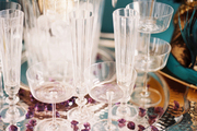 A serving tray of clear glassware and champagne on ice