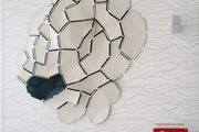 An abstract wall piece on patterned wallpaper with a red side table sitting in the corner of the room.