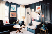 Black walls and dark furniture in a living space filled with art