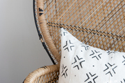 A detail of a black and white pillow on a wicker chair.