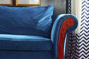A detail of a velvet rolled arm sofa, accented by framed bug prints, chevron curtains and an overdyed rug.