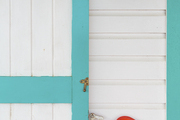 A rustic tin sconce against pastel-trimmed clapboard siding