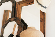Layered wood-frame mirrors on a white shelf